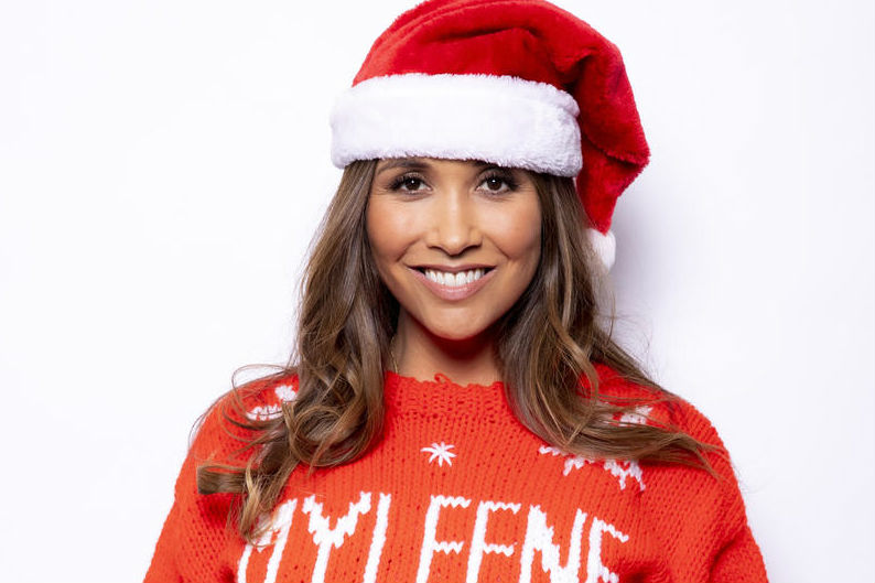 Myleen Klass, wears a santa hat and her personalised Christmas Jumper for Save the Children