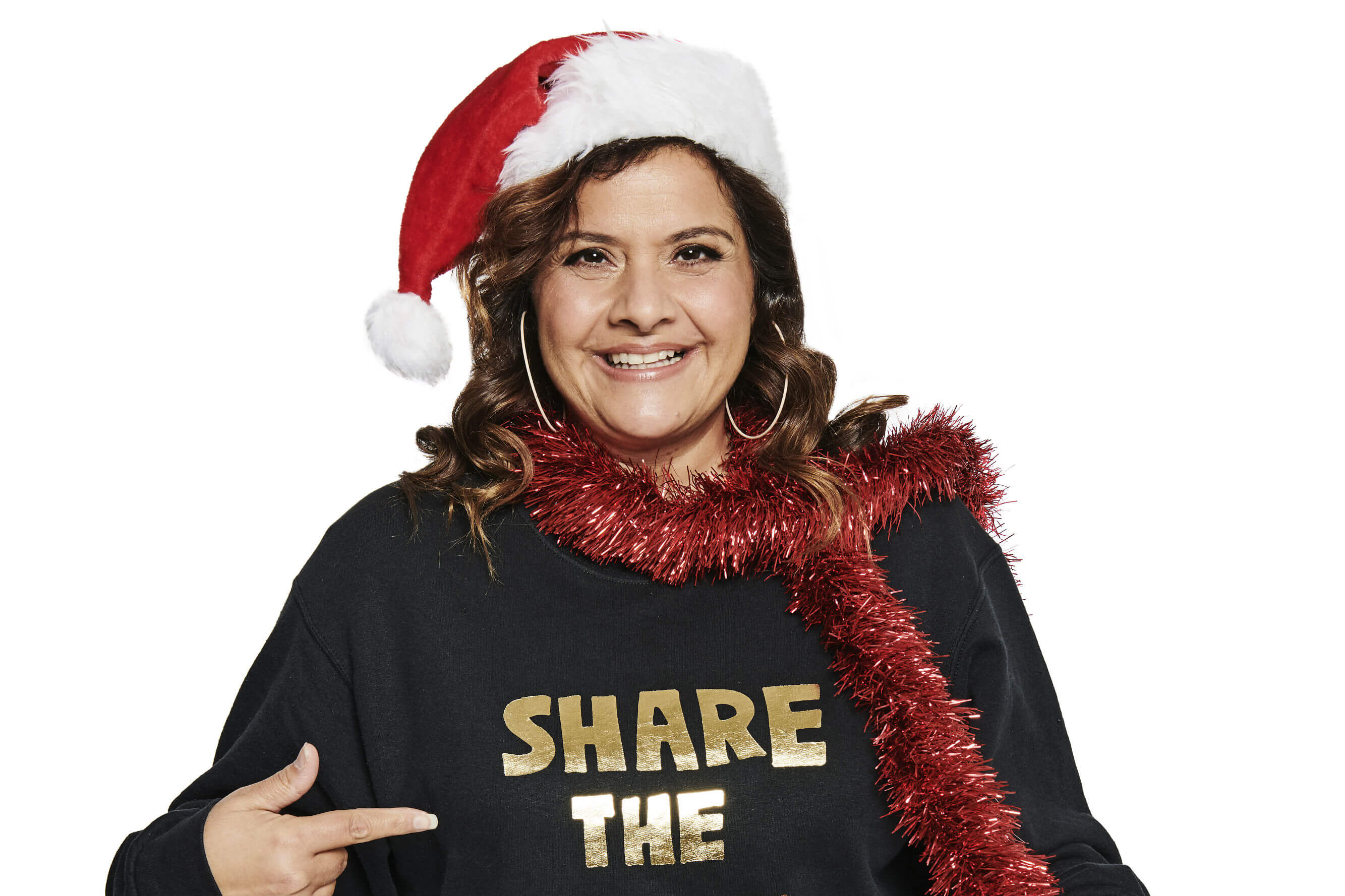 Nina Wadia dresses in Share the Love Christmas Jumper and tinsel for Save the Children's Christmas Jumper Day.