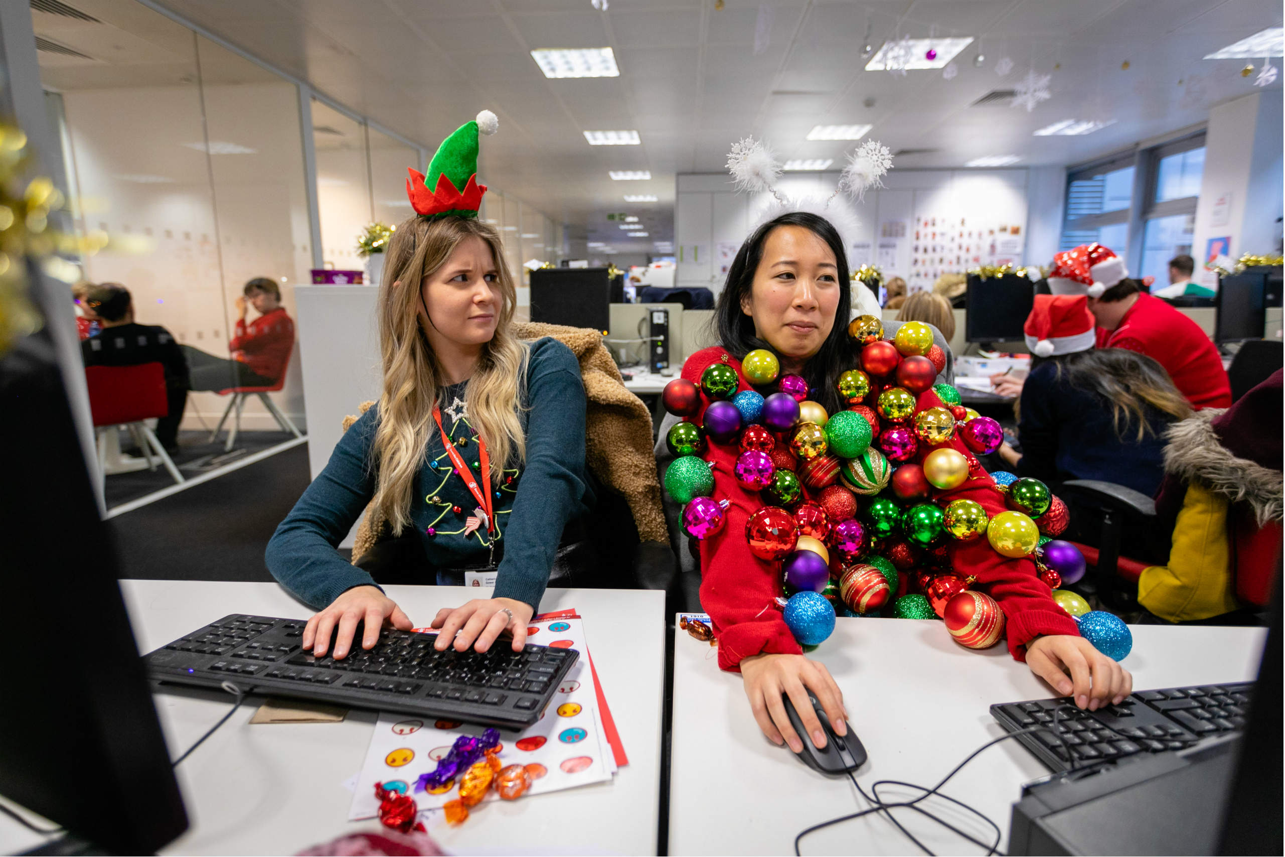Office workers on their computers in silly jumpers
