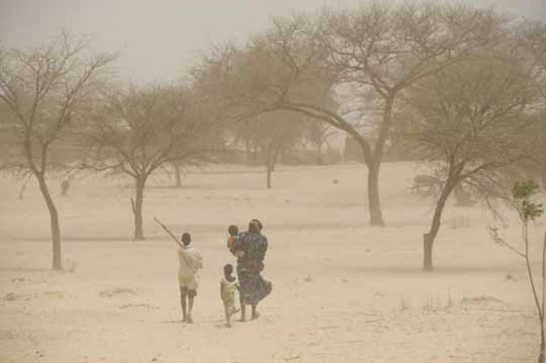 Baraka walks through a sand storm to her village with three children