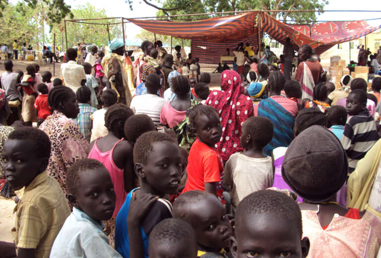Children and families wait to be registered by Save the Children staff in Wunrok, southern Sudan.