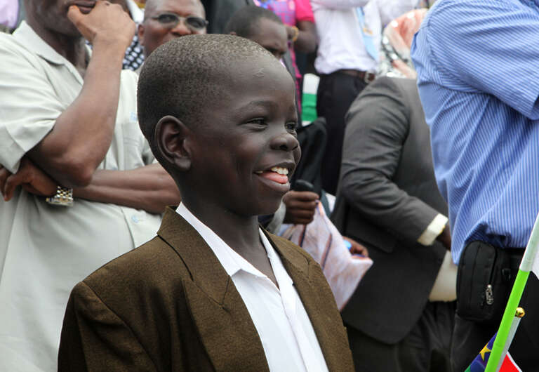 A young boy smiles and sings along to the new Republic of South Sudan national anthem during the independence ceremony