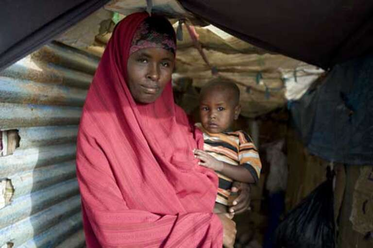 Norta Omar, 26 with her youngest child Faisal Kasim, two. Norta left south central Somalia after her 100 goats and 50 cattle had died.