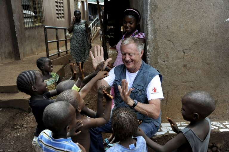 Chris Tarrant plays with kids near Kroo Bay clinic, Sierra Leone, For Born to Shine on ITV.