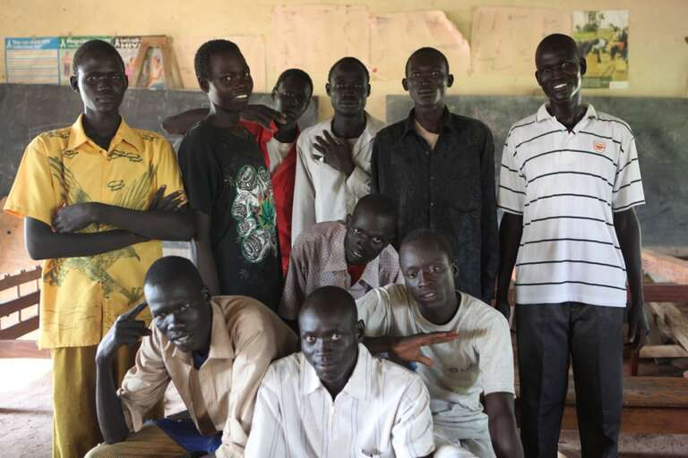 Carpentry instructor and former graduate, Emmanuel Yak Bol, 26, with his carpentry students at the Technical and Vocational Education Training (TVET) Centre.
