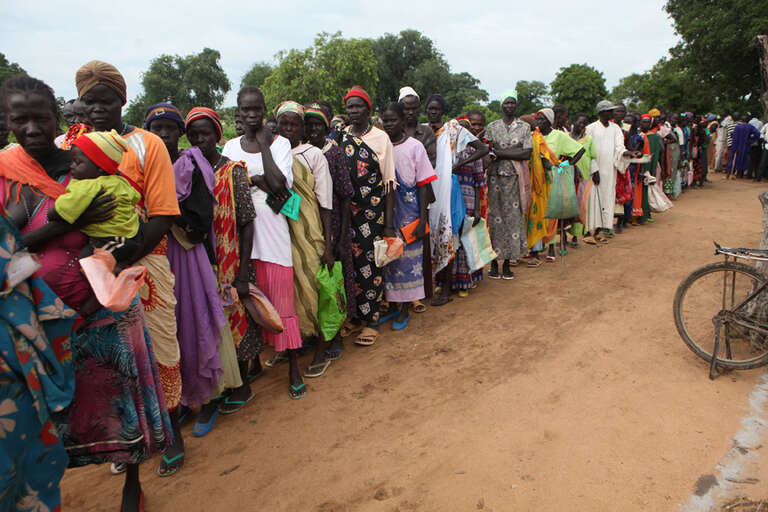 Cash-for-work and cash transfer beneficiaries wait in line to receive their monthly 80 SSP from Save the Children at the Warawar distribution site.