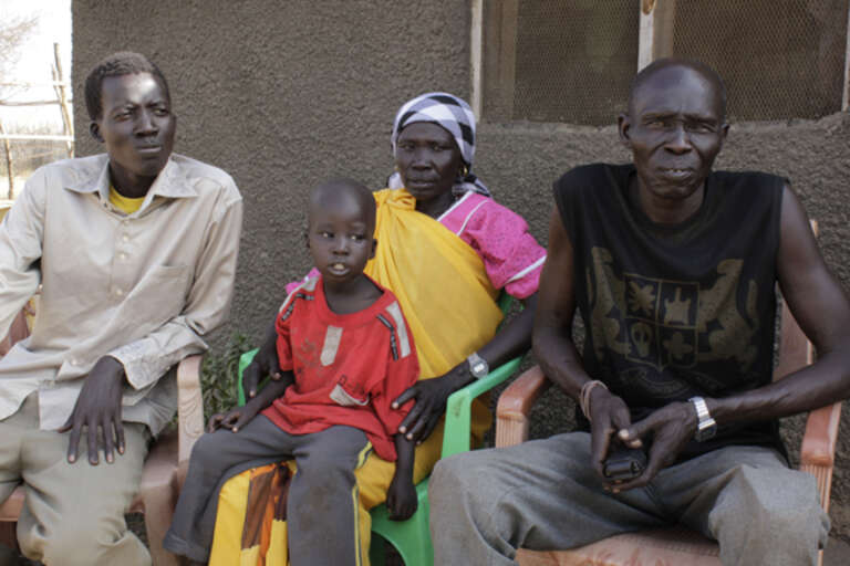3 year old Ulu with his uncle Bal and extended relatives, in Juba.