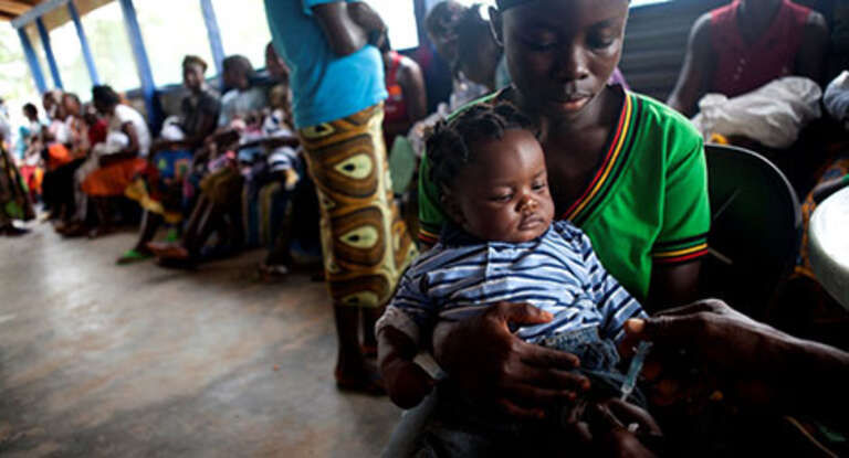 A mother holds her son as he is vaccinated at a health clinic in Totota, Liberia.