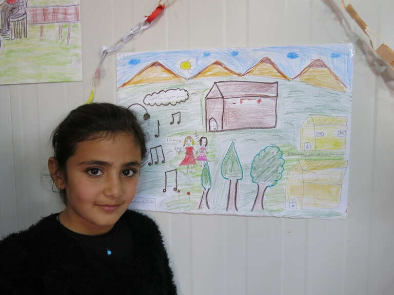 A Syrian child in Domiz refugee camp, Iraq, photographed with her drawing on children's rights