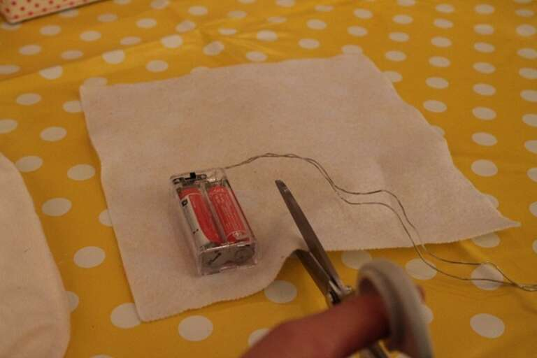 Cut a square of fabric 2cm larger than your battery pack