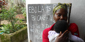A mother and child at a rural centre in Freetown where Save the Children is teaching communities how to limit the spread of Ebola