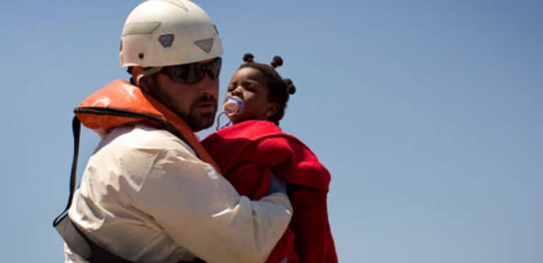 A rescue worker tends a young migrant girl after she was rescued by a Spanish coast guard vessel in the port of Tarifa