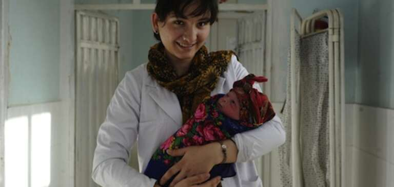 Afghan midwife holds newborn baby