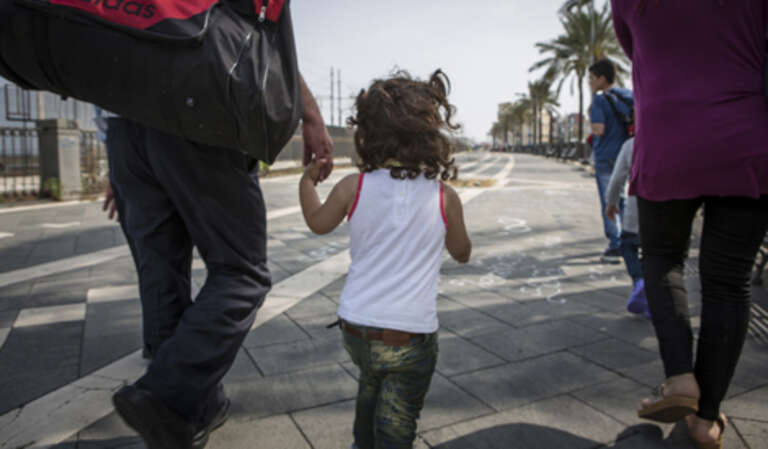 Syrian refugees walk with their children through the streets of Catania, Italy, to find a place to sleep for the night.