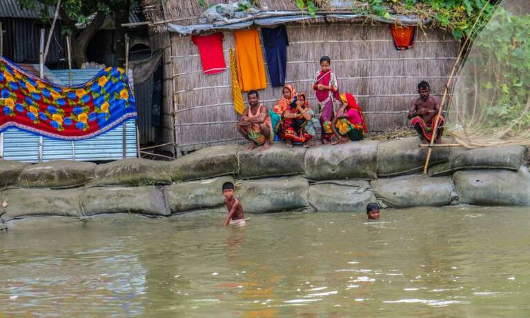 Children play in floods of water where their homes used to stand.