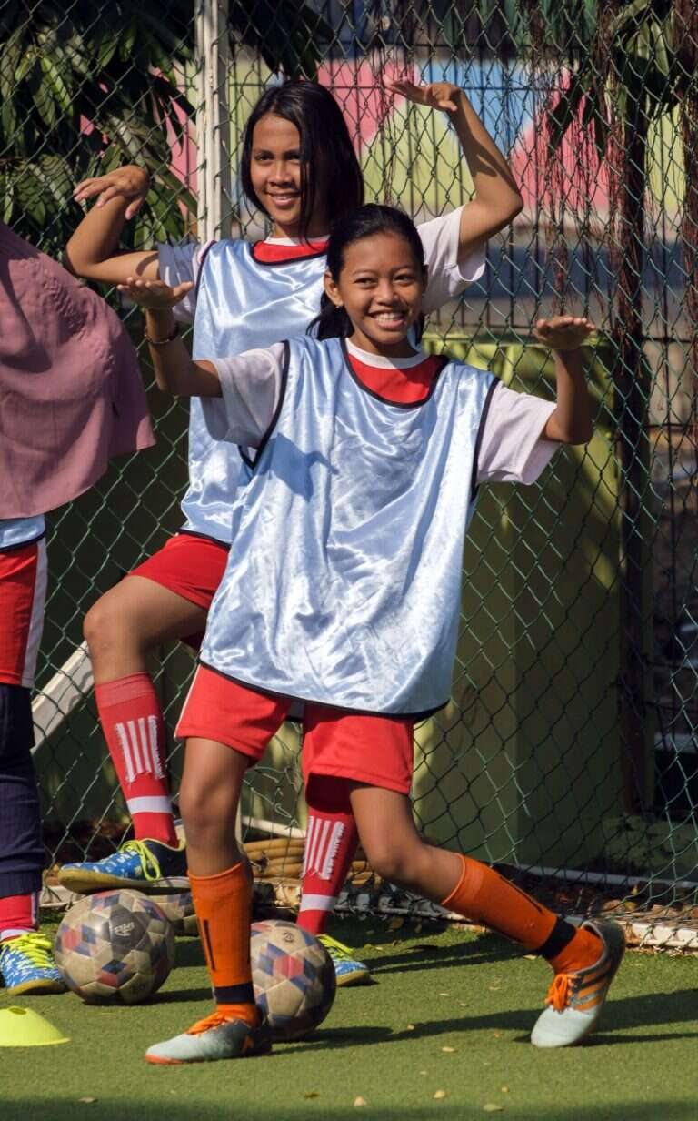 Diah, 14, a participant in the Coaching for Life Programme in Jakarta Indonesia, strikes a pose with a fellow team mate.