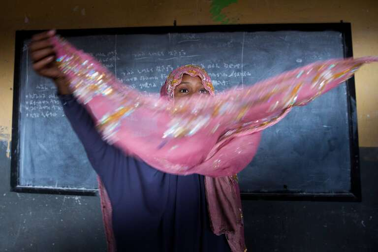 Anti-FGM campaigner Nura stands in front of the chalkboard, her pink headscarf frozen by the photograph as she adjusts it with a sweeping motion in front of her