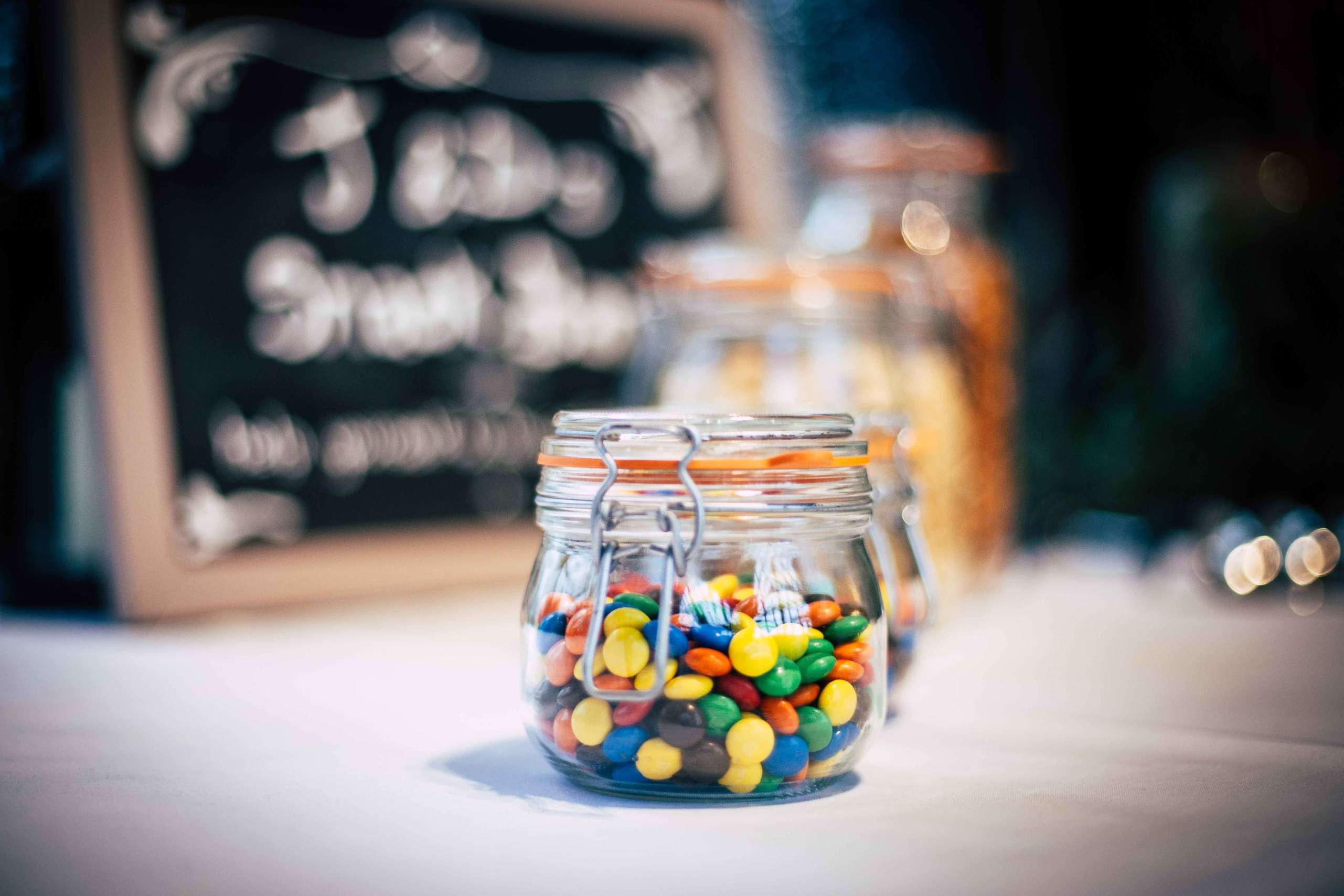 A glass jar filled with smarties.