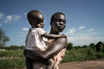 Teenage mother Joy and her daughter Annette outside their home in Bidi Bidi refugee settlement