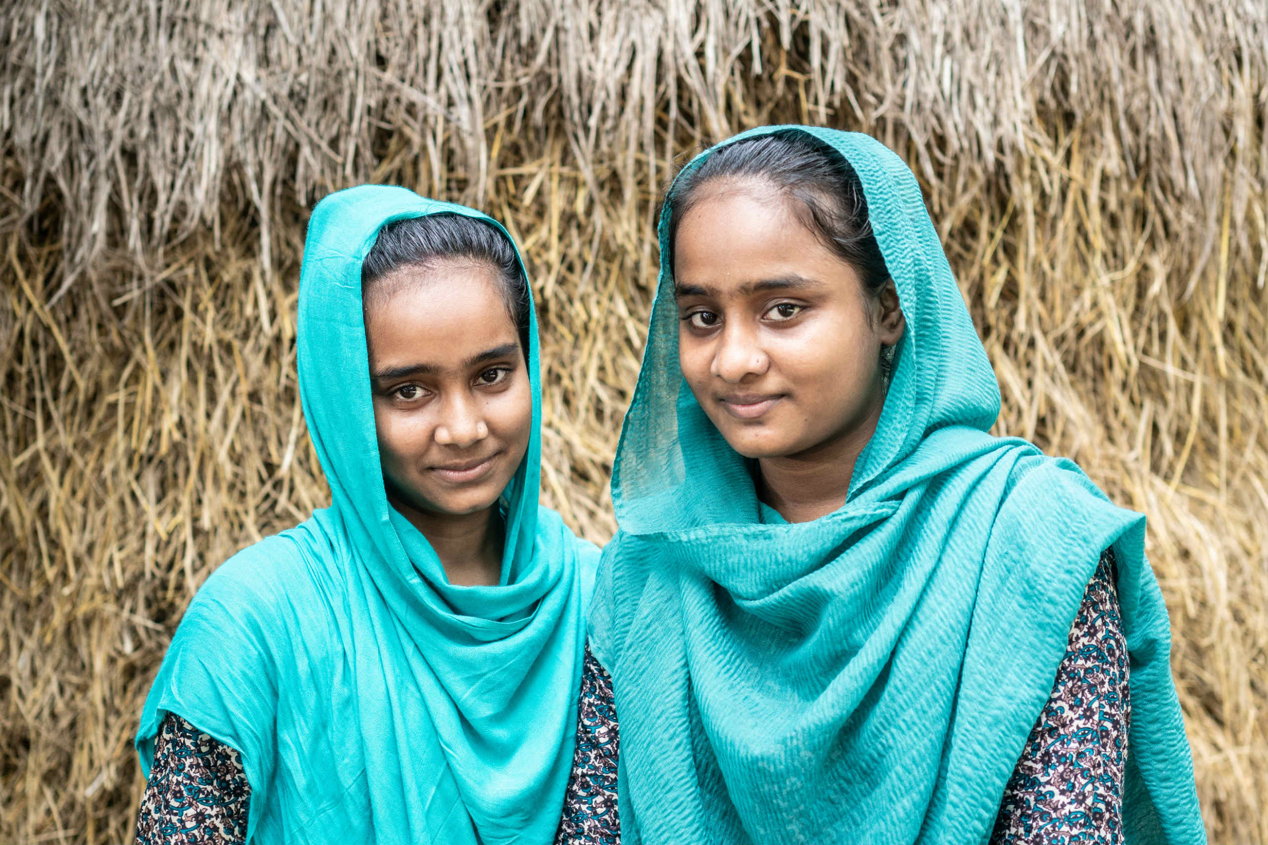 Runa, 17, stands with her sister Shuma, in their community in Sylhet, Bangladesh