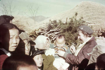 A Save the Children worker with children and mothers in the aftermath of the Korean War.