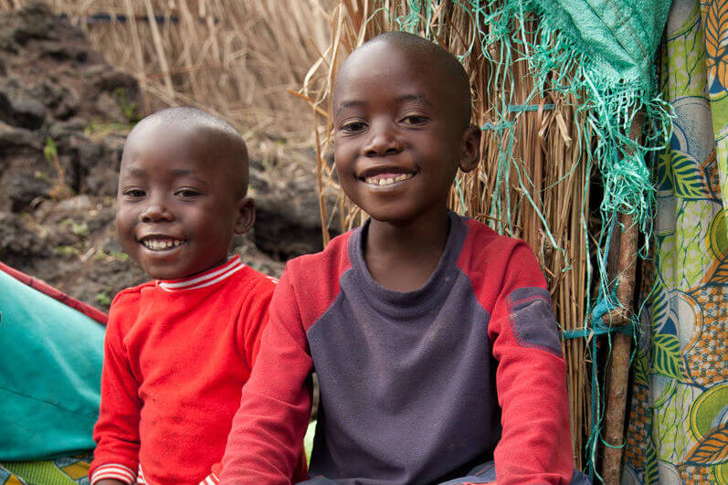 Baraka, 7, and Kibonge, 4, sit smiling outside their tent in a camp near Goma, the provincial capital of North Kivu