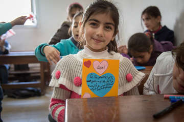 A child holds up the Mother's Day card she made during a Mother's Day activity at a community school for Syrian refugee children in Cairo