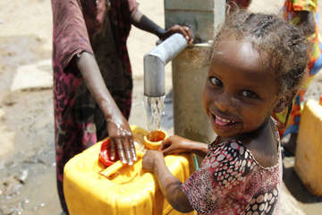Young children in Ethiopia fill up plastic water barrels in December 2015.