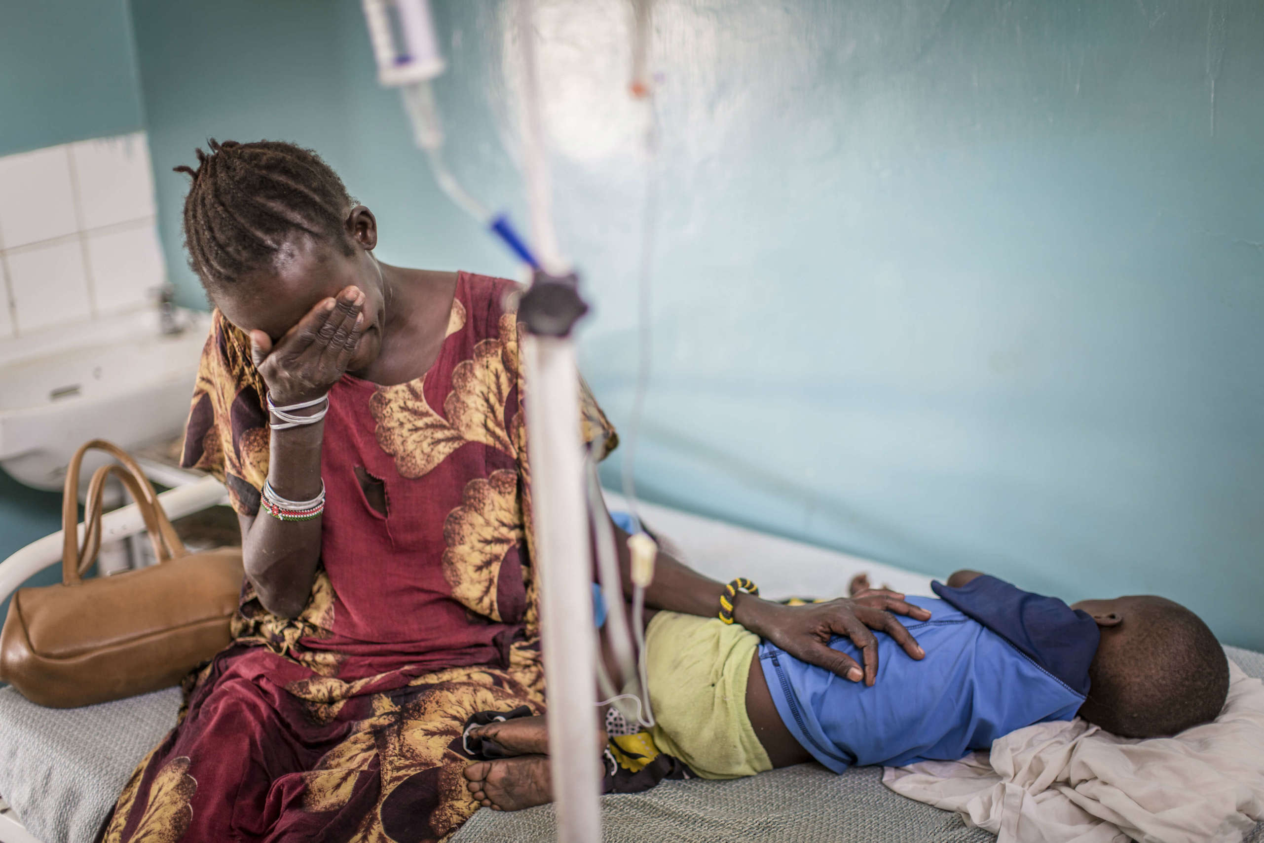 Maximilla sits by the bedside of her son, Jackson, as they wait for the medical treatment to take effect.