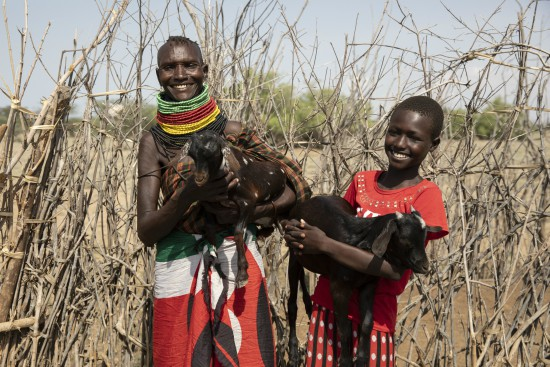 Veronica and her daughter hold the two goats they have been able to buy with support from save the children