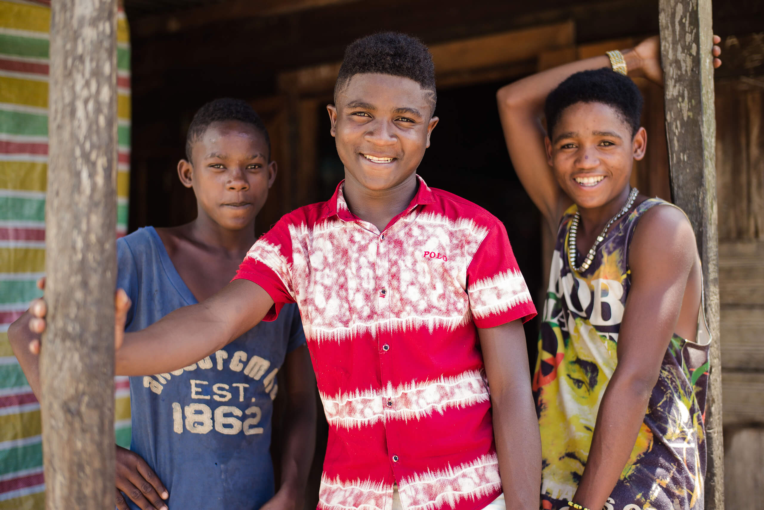 Bolo, 18 (centre), stands with friends Barthez, 17 (left) and Narco, 15 (right) from the youth association in their village in the Sava region of Madagascar