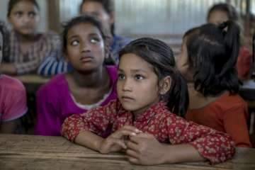 In our Child Friendly Space in Sindhupalchok, Nepal, seven-year-old Mina and her two sisters, listen to a teacher talk about child trafficking dangers.