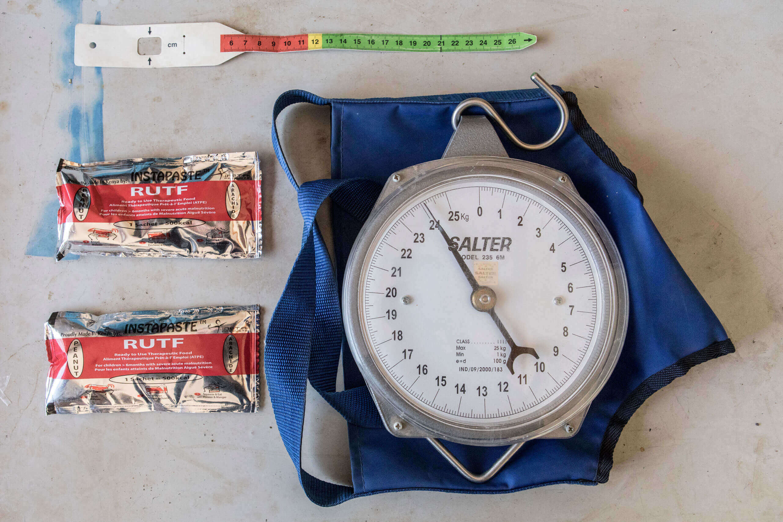 MUAC arm band (top), Ready to Use Theraputic Food/RUTF (left), child weighting scales (right). Kapoeta County, South Sudan.