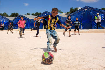 "Syrian children play football in a ""child friendly space"" in one of the camps for displaced people in northwest Syria, close to the Turkish border."