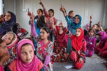 A group of girls put their hands up to give the teacher the answer to a maths question inside a classroom at Save the Children's temporary learning space in Qayyara Air Strip IDP Camp.
