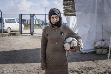 Sara*, 14, holding a football at our Child Friendly Space.