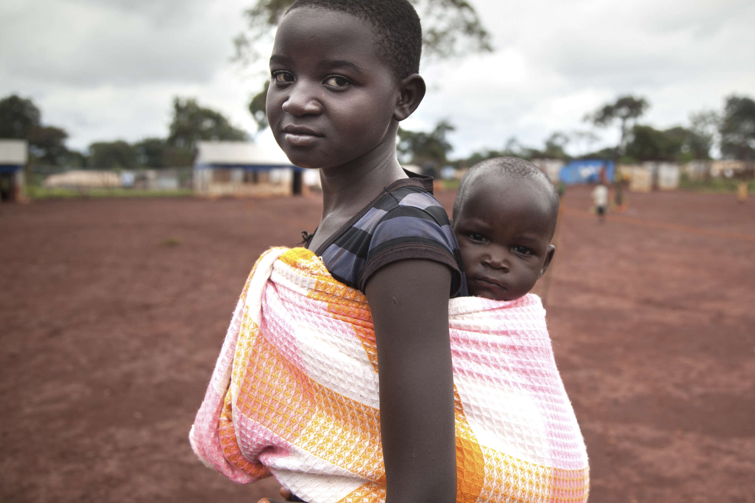 Spesios carrying a baby in Save the Children's Child Friendly Space, Burundi.