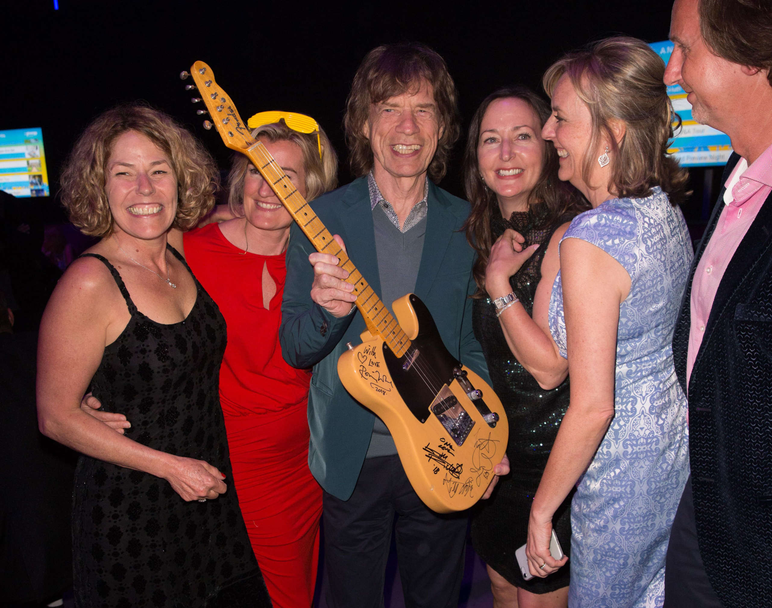 Sir Mick Jagger of the Rolling Stones with the guitar he auctioned for a staggering £70,000