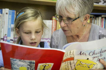 A volunteer reads with Jemima, 6, as part of the Born to Read programme.