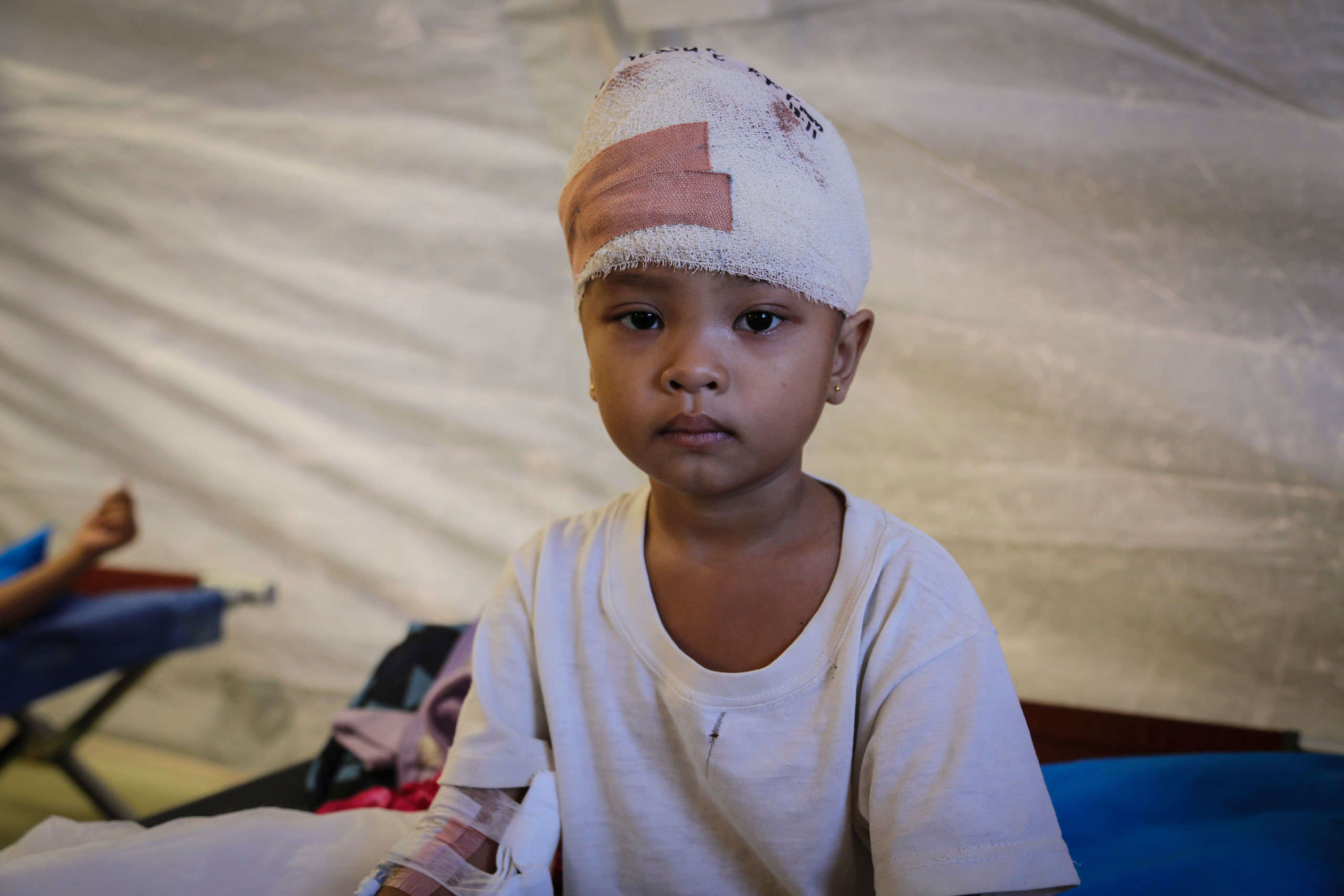 Alisa, aged 4, waits with her mother for her second operation to fix her skull after a piece of wood became lodged there during typhoon Haiyan. Australian and British doctors performed the surgery.